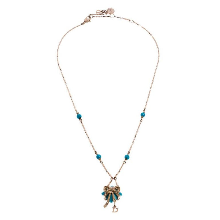 Dainty and elegant, this necklace from Dior is a versatile beauty that can be worn to any occasion. This necklace features a gold-tone chain that holds beads and a pendant that looks like a wrapped present. Gift yourself this piece today!  Includes: