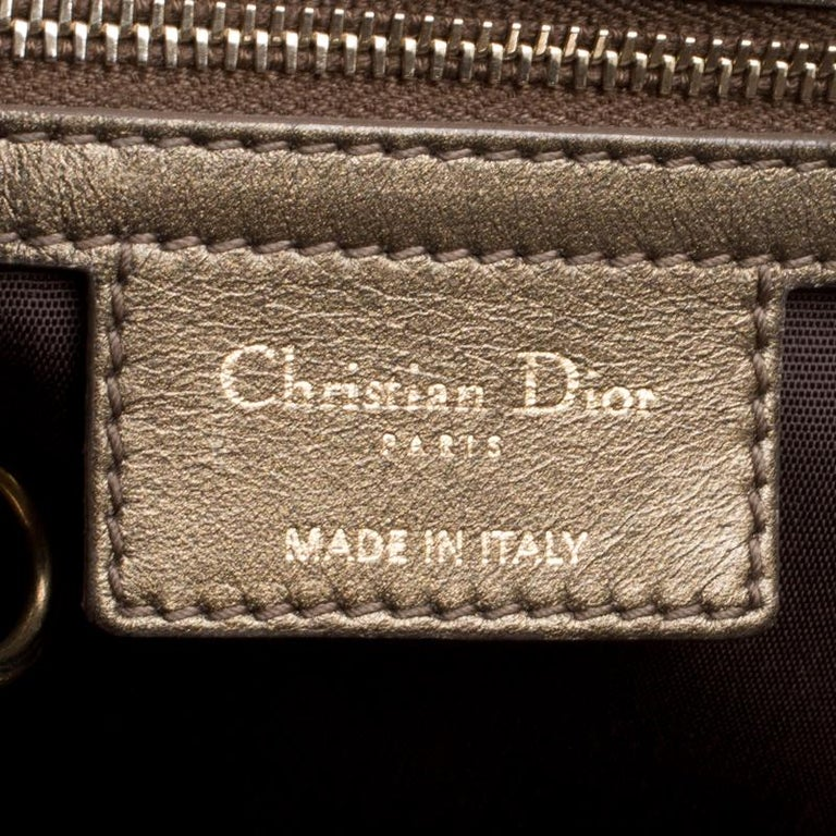 This shopper tote from Dior is a timeless piece. The bag comes in a luxurious coated canvas exterior in bronze hue with gold-tone hardware and Dior letter charms. It features double top handles and protective feet at the bottom. A buttoned closure
