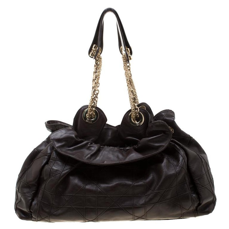 This stylish Le Trente hobo from Dior has been crafted from brown leather and styled with their signature cannage pattern. The bag features dual chain handles with leather shoulder rest, a CD cutout charm, a drawstring closure and protective metal