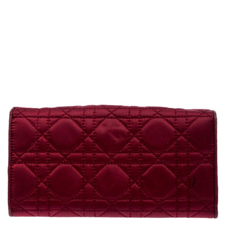 This beautifully designed Dior wallet will perfectly team up with any day or night outfit. The wallet is crafted from burgundy satin and it features Dior's iconic Cannage quilted pattern giving the bag a beautiful texture. The exterior is finished