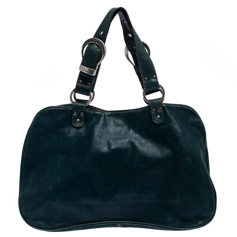 From the house of Dior, this Gaucho Double Saddle bag is an excellent blend of elegance and style. It comes in a green color that is perfect for making a statement. The bag is crafted from quality leather and features a chunky buckle, medallion, a