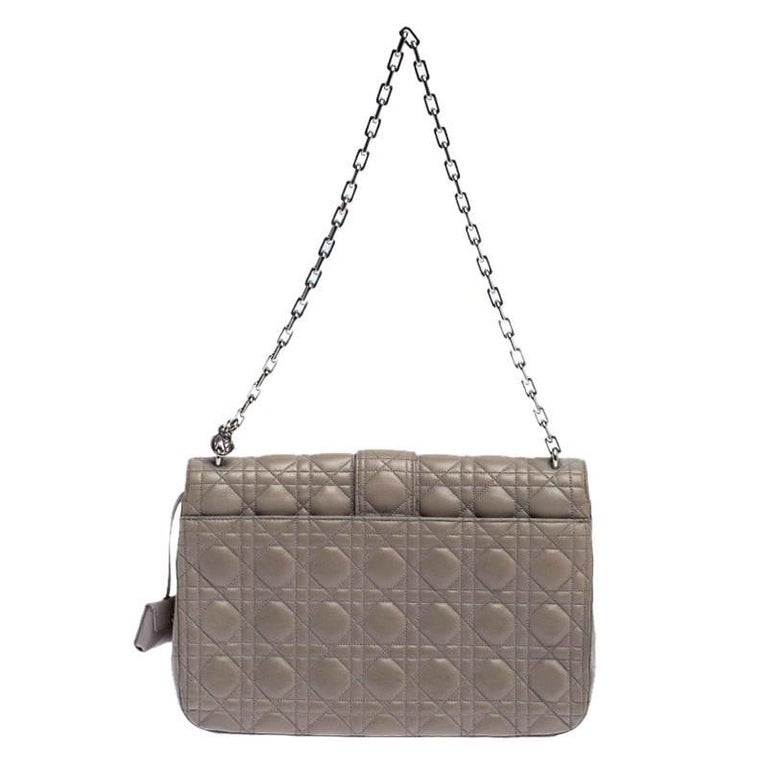 Flap bags like this Miss Dior will never go out of style. Crafted from leather, this Dior flap bag features a grey Cannage exterior and a chain strap. The front flap has a Dior lock that opens to a leather-lined interior with enough space to keep