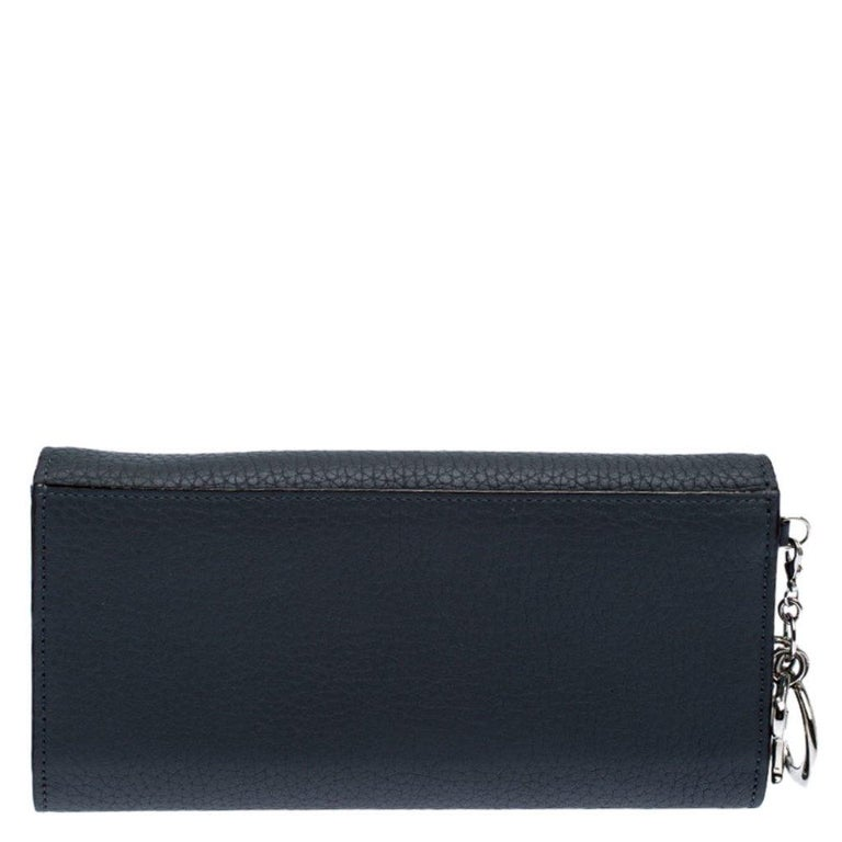 This Dior wallet will help you store your cards and cash in style. Made from leather, it features silver-tone Dior charms contrasting with the grey shade. Its envelope design has a snap-enclosed flap closure that opens up to a leather and