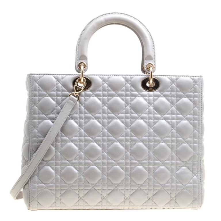 The Lady Dior tote is a Dior creation that was designed in 1994 and has gained lovers worldwide. Crafted from grey leather this tote carries a cannage pattern exterior. It is equipped with dual rolled top handles, a shoulder strap, classic Dior