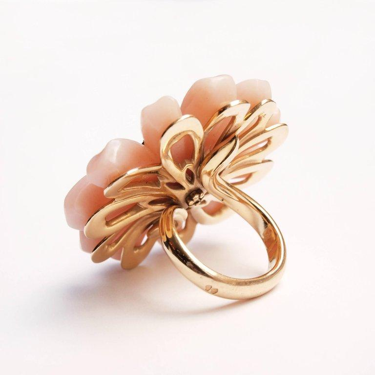 A Christian Dior pink opal and diamond ring designed by Victoire de Castellane. The brilliant-cut diamond stamen cluster centre to carved pink opal petals, the hoop forming the stem size L, in maker's box. A stunning piece of jewellery