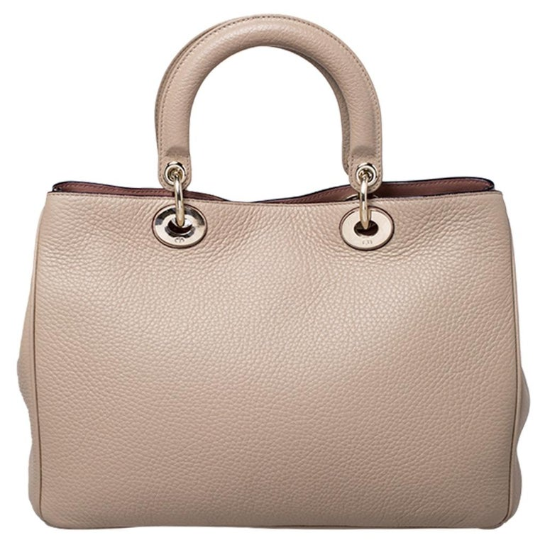 The Diorissimo shopper tote from Dior is a piece that has never gone out of style. The leather bag comes in a light beige shade with gold-tone hardware and Dior letter charms. It features double top handles and protective feet at the bottom. A snap