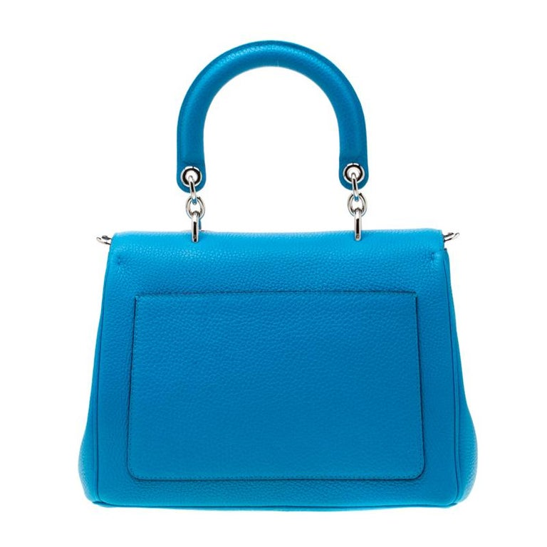 Flap bags as gorgeous as this one from Dior will never go out of style. This small Be Dior bag has a lovely silhouette and a chic appeal. It has been meticulously crafted from leather and equipped with a single rolled top handle, a removable