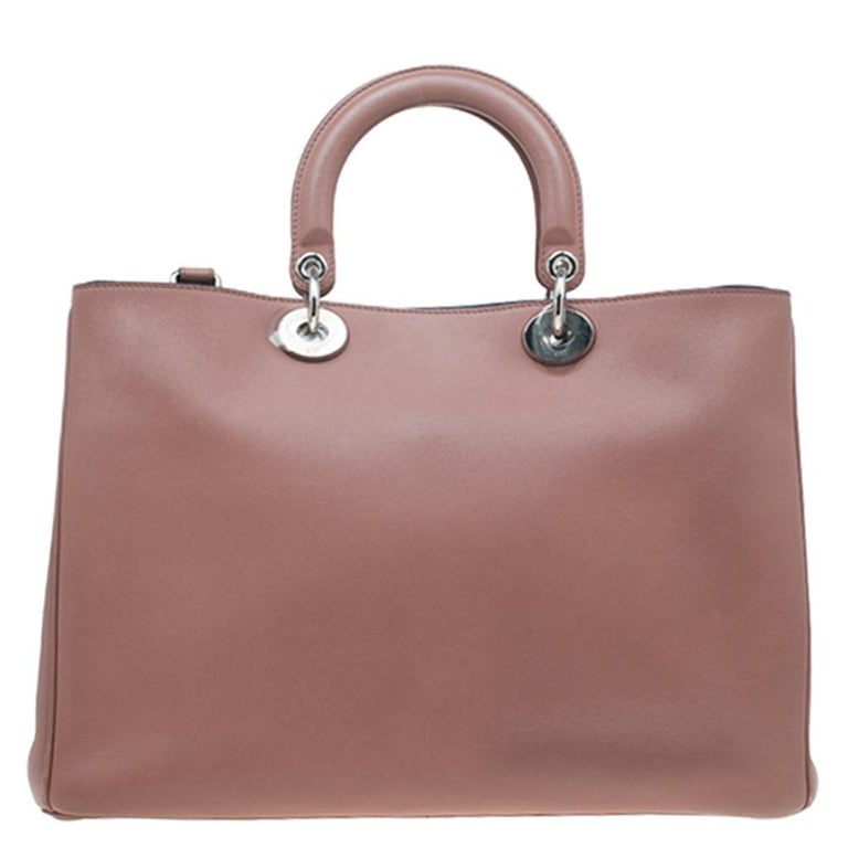 This large Diorissimo shopper tote is a classic Dior creation and is super chic yet practical. It features a smooth gorgeous light brown leather exterior with two leather top handles and a detachable shoulder strap. It comes accented with