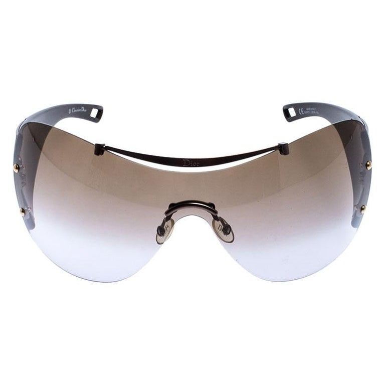 Block out the sun and keep your eyes protected wearing these stunning Dior shield sunglasses. Constructed from acetate and metal, the frame and arms have metallic hues. This pair features brown lenses and logo detailing along the temples to complete