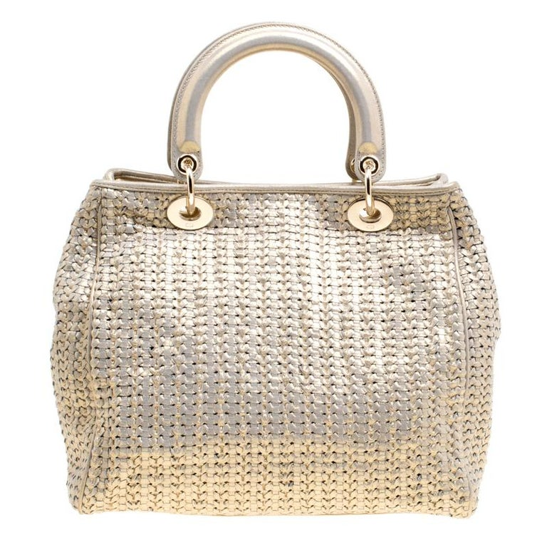 This sophisticated and feminine Lady Dior tote in your hand is apt for the perfect Dior look. Crafted from leather, this metallic gold tote is accented with a woven pattern and gold-tone hardware. It features signature Dior charms, two round handles