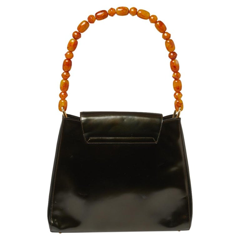 Every modern-day wardrobe needs a Dior handbag like this. A practical and elegant everyday bag in a lovely metallic olive green color, this one is made from glossy leather. It is held by a single pearl handle, features gold-tone hardware, and comes