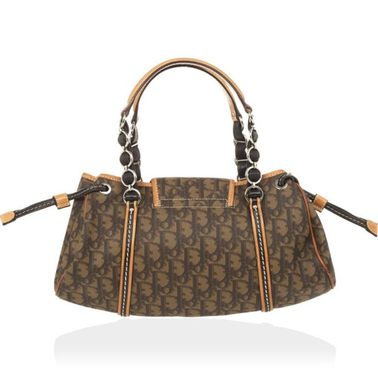 Carry this charming Trotter Romantique satchel by Dior everywhere. With an exterior made from Dior's monogram canvas and leather trim, it is beautifully detailed with a bow, a Dior heart lock and embellished handles. The interior is lined with satin