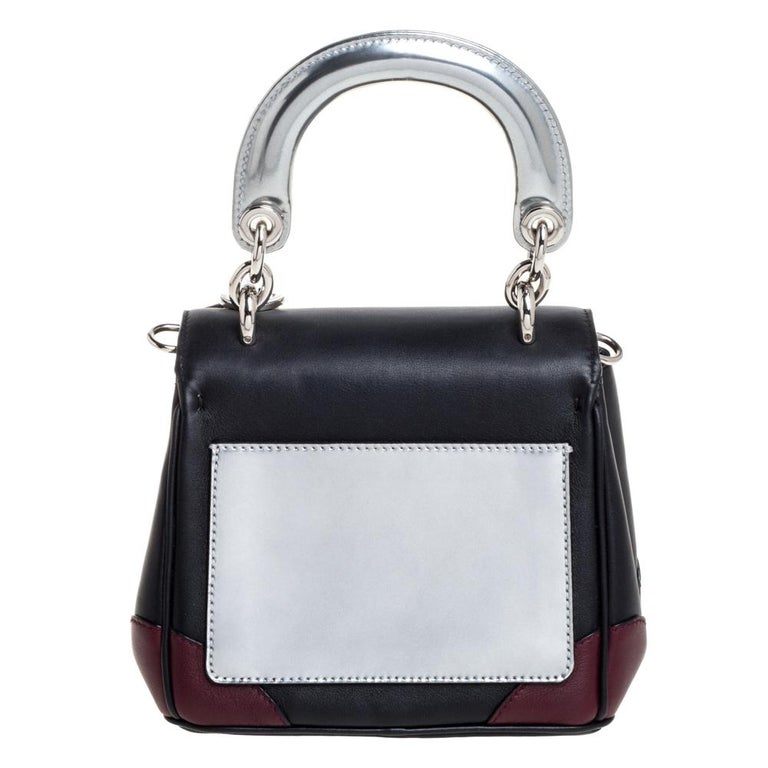 This Be Dior bag from the house of Dior is sure to add sparks of luxury to your wardrobe! It is crafted from multicolored leather and features a chic silhouette. It flaunts a single rolled top handle with attached 'DIOR' letter charms and comes