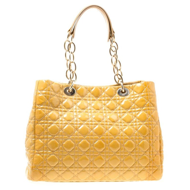 This Dior shopping tote is exceptionally charming. The shiny patent leather accented with the signature cannage pattern makes it look stylish and trendy. This bag features D-I-O-R dangling letter charm in gold-tone hardware on the front lug, metal
