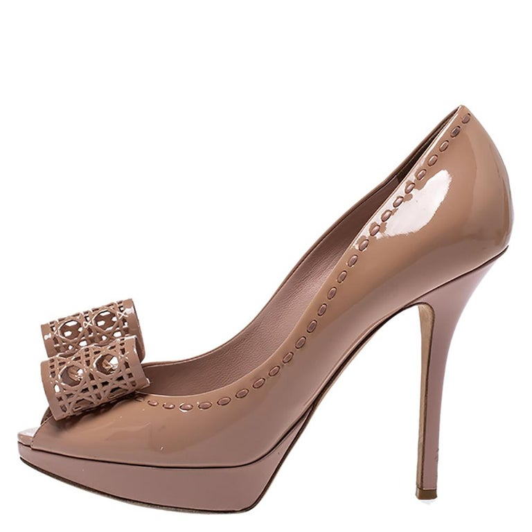 Add a classic air to your ensembles with these stylish & feminine pumps from Dior. Crafted in Italy, they are made from nude beige leather ad come with peep toes. They are styled with signature Cannage cut-out bows and gold-tone hardware on the