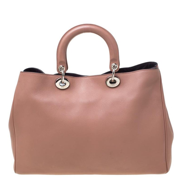 The Diorissimo tote from Dior is a timeless piece. The leather bag comes in a luxurious old rose hue with silver-tone hardware and Dior letter charms. It features double top handles, a detachable shoulder strap and protective feet at the bottom. A