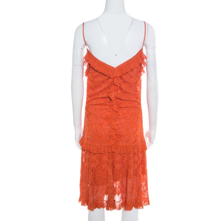 Make the crowds go gaga over you and win every possible praise in this gorgeous dress from Dior! This sleeveless orange creation is made of a viscose blend and features a perforated lurex knit design. It flaunts a flattering feminine silhouette and