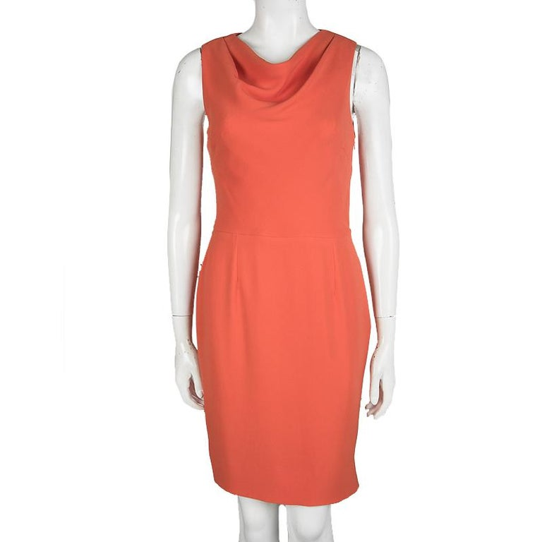 This pretty sleeveless dress is by Dior. Made from silk, the orange dress has a cowl neck and a slit at the back. A cute pair of ballet flats or strappy sandals will complement the dress beautifully on any day.  Includes: The Luxury Closet
