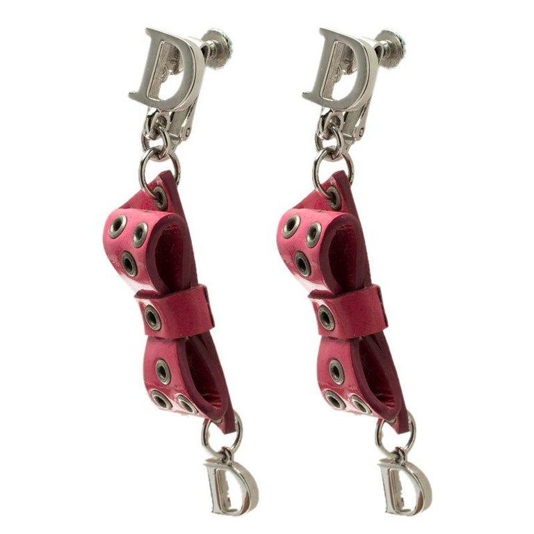 Look pretty in these pink drop earrings from Dior. An artsy piece, 'D' studs hold the pink rivet leather bow that makes the body of the earrings. Silver-tone 'D' additions dangle down from the leather bows and add to the length and look. A cute pair