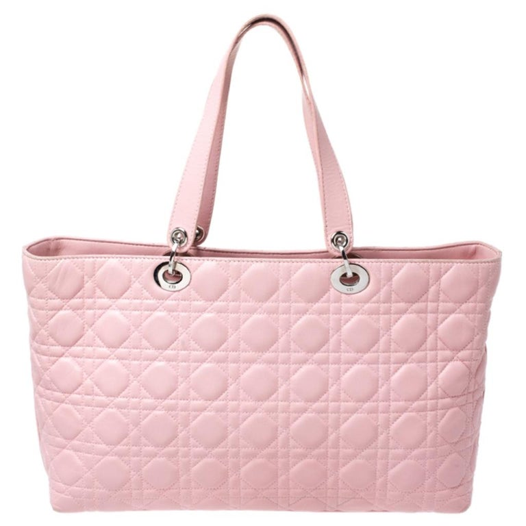 This Dior tote is exceptionally charming. The pink leather accented with the signature cannage pattern makes it look stylish and trendy. This bag features D-I-O-R dangling letter charm in silver-tone hardware on the front lug, two leather straps and