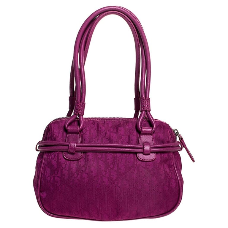 This Dior handbag promises to take you from day to night and weekday to weekend. It is crafted from nylon and leather and showcases the brand's signature monogram throughout. The exterior is beautified with a bow detailing with the ends features the