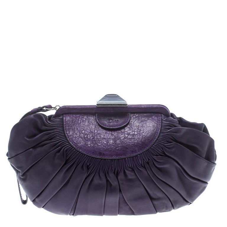 This frame clutch by Dior is crafted from purple leather and features pleats on the exterior. Its construction provides long-lasting use and it comes with a wristlet. The interior is canvas lined and will safely hold your belongings.  Includes:
