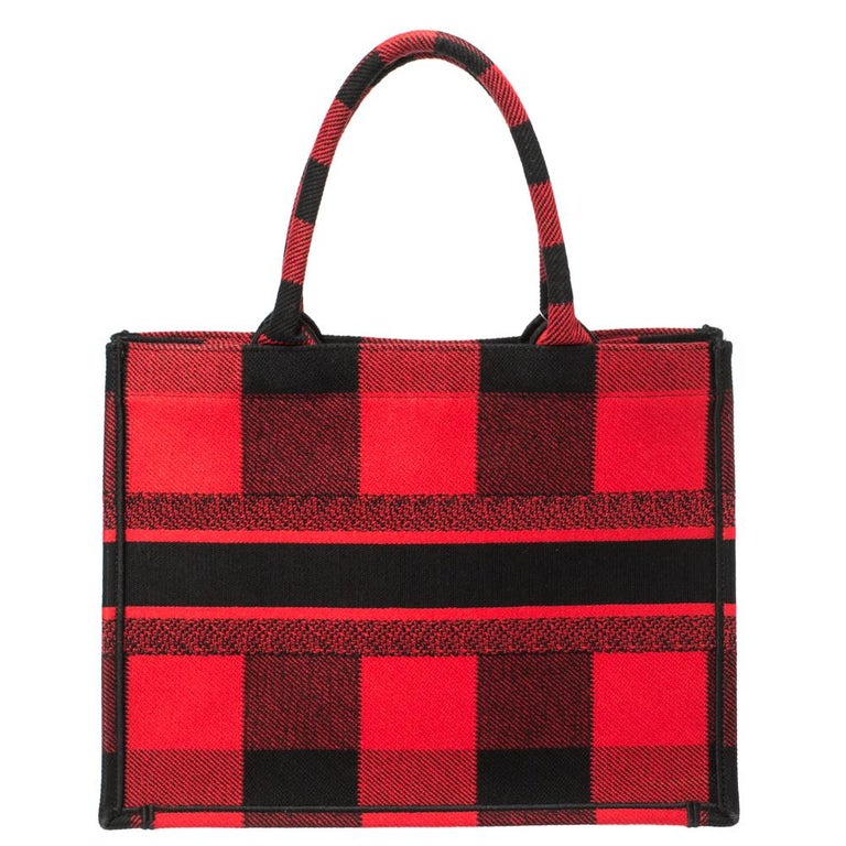 Designed by Maria Grazia Chiuri, the Dior Book Tote is a travel accessory for people with style. The bag here is crafted from canvas into a beautiful structure and covered in plaid patterns all over. Two handles, the 'Christian Dior' signature, and