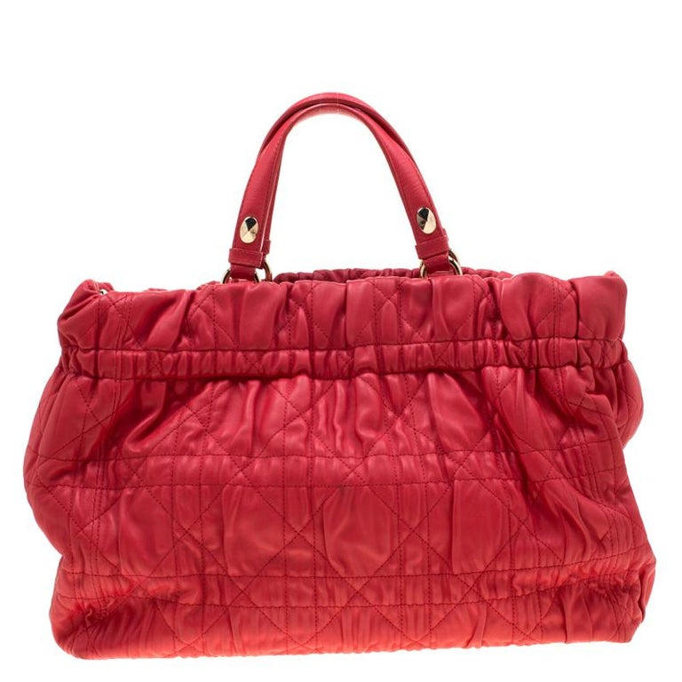 This chic bag from Dior is crafted from leather and features quilted Cannage detailing on the exterior. The red tote comes with dual handles and a leather chain strap. The buttoned closure opens to a matching leather-lined interior that has a zip