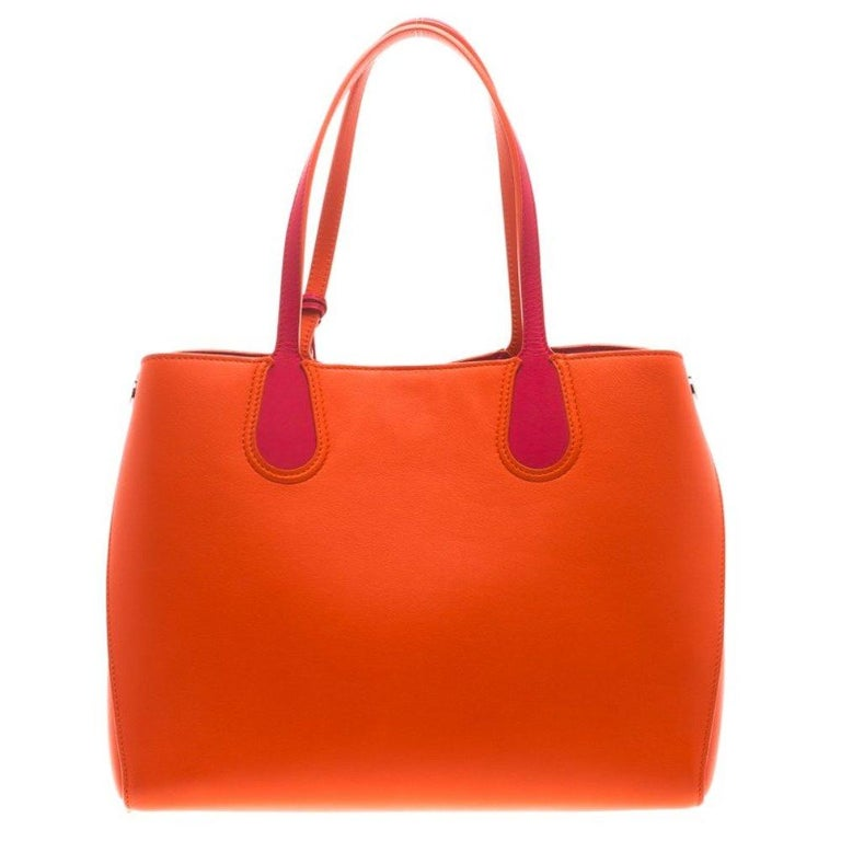 This shopping tote from Dior is a timeless piece. The bag is crafted from red orange leather and features dual handles, protective feet at the bottom and Dior letter charms. A top buttoned closure opens to a leather lined interior and the bag is