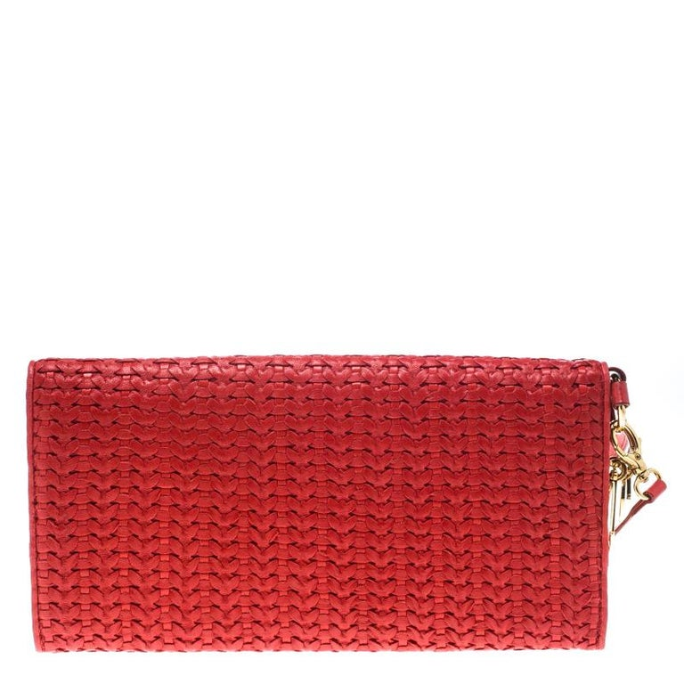 Brimming with elegance and shining with beauty is this beautiful clutch by Dior. It has been crafted from woven leather and designed in a red shade with their signature CD charms in gold-tone dangling on the sides. Complete with fabric-lined