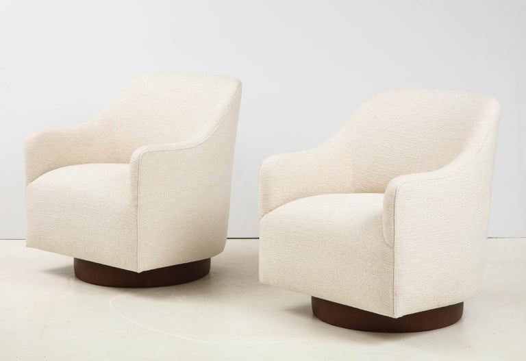 Pair of tilt/swivel club chairs by Milo Baughman for Directional featuring new ivory boucle upholstery and brown leather wrapped base. Chairs are generous in size and have a streamlined sleek profile. New padding, foam.