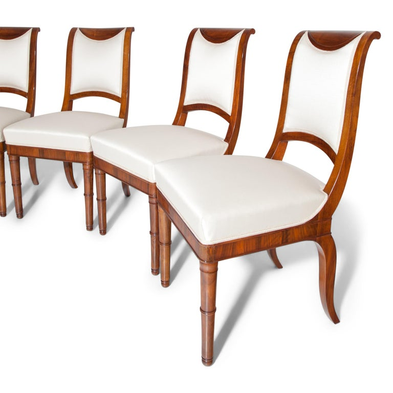 Four French Directoire walnut chairs with a cushioned S-shaped backrest and a trapezoidal seat, standing on conical feet in the front and saber legs in the rear. The chairs were professionally refurbished and reupholstered with a high quality beige