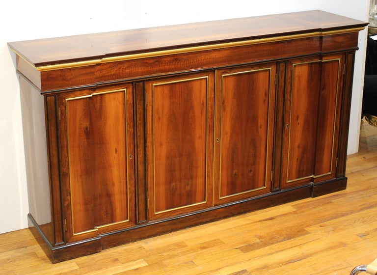 Directoire style mahogany sideboard or console, shaped top over double swing doors at center flanked by single doors, brass mounts. Measures: 36