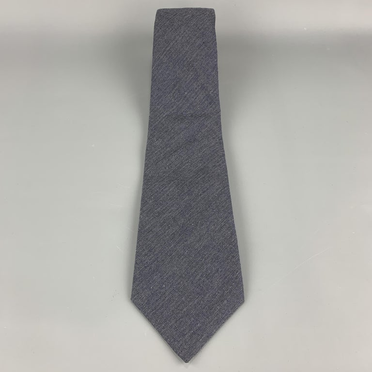 DIRK BIKKEMBERGS necktie comes in muted navy blue cotton with all over herringbone print. Made in Italy.  Excellent Pre-Owned Condition.  Width: 3.75