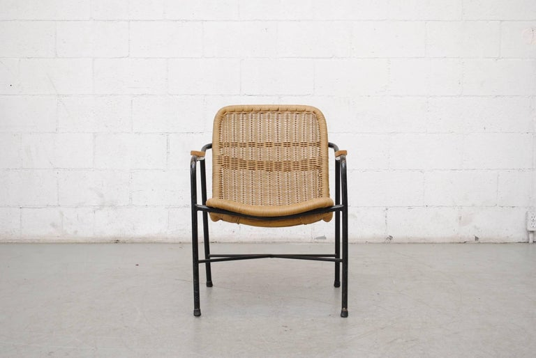 Beautiful low back woven rattan seat on a black enameled metal frame and wood arm rests by Dirk Van Sliedregt in good original condition..