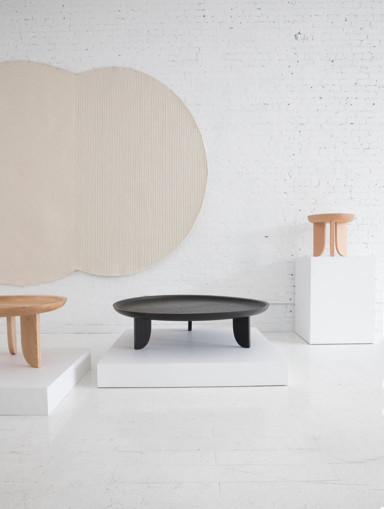 Taking inspiration from hand carved African stools, a scooped out tabletop is created with a little help from technology. A CNC router is used to cut away the wood bowl leaving behind a slope that quickly levels to a flat surface.