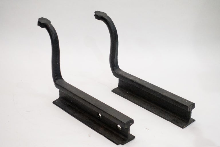 Wonderful pair of antique Folk Art snake andirons with inset glass eyes. They were blacksmith made of hand-hammered wrought iron. The artist used pieces of railroad rails to build one of a kind set of heavy powerful andirons. These were built to