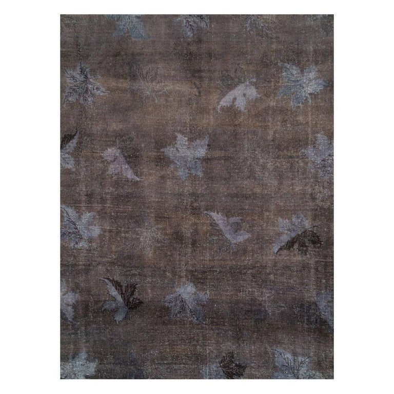 This 21st century creation consists of a vintage Persian Mashad rug handmade during the mid-20th century that was scraped and overdyed charcoal to produce a distressed appeal. Although the look is distressed, the rug is in very strong and durable