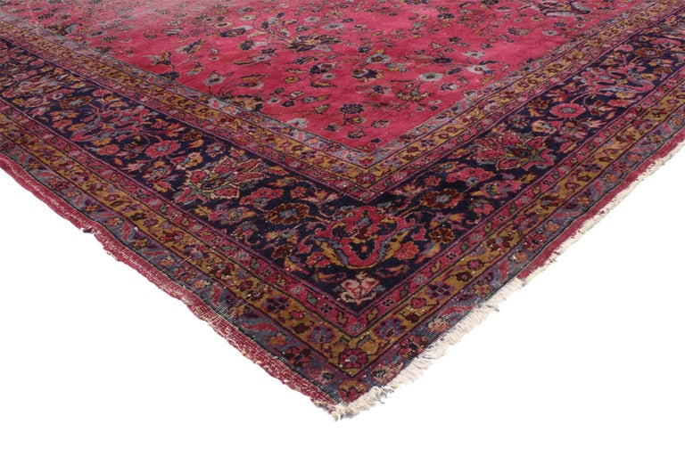 76756, distressed antique Indian Palace rug with Victorian style and Mughal design. This hand knotted wool antique Indian palace rug features an all-over floral pattern spread across an abrashed ruby red field. Drawing inspiration from traditional