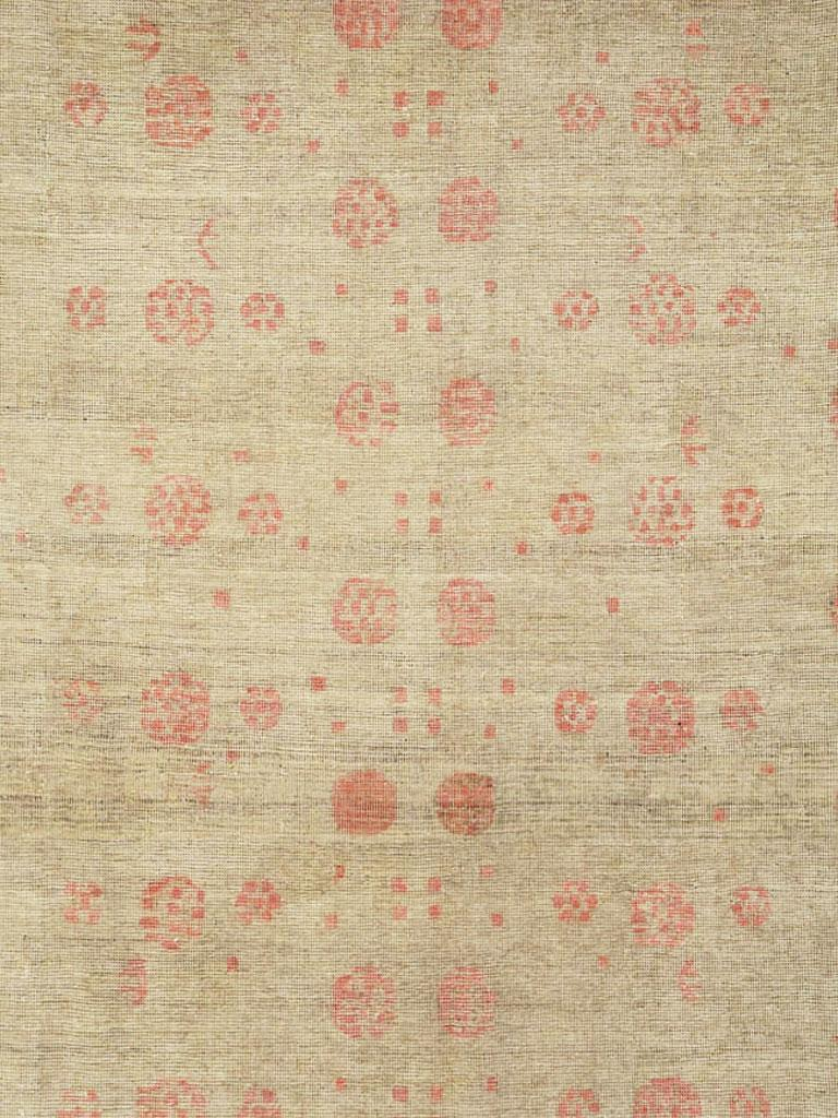 An antique East Turkestan distressed Khotan carpet in gallery size format from the early 20th century. The beige field of this Xinjiang province (western China) oasis town rug displays two columns of the characteristic vase and pomegranate tree