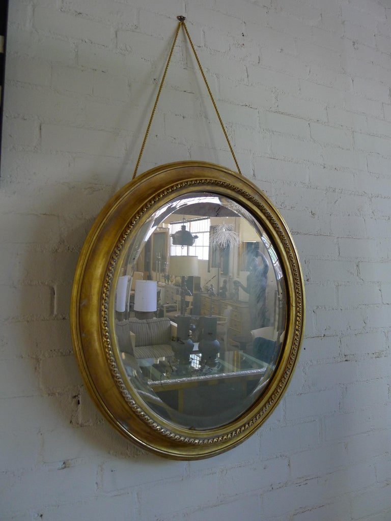 Oval gilded mirror in a classic antique style, with new distressing, new rope and new 22K gold finishes for the frame. Mirror is antiqued see all imaging. Hung by rope.  The wood frame has age marks and cracklature throughout, indicative of the