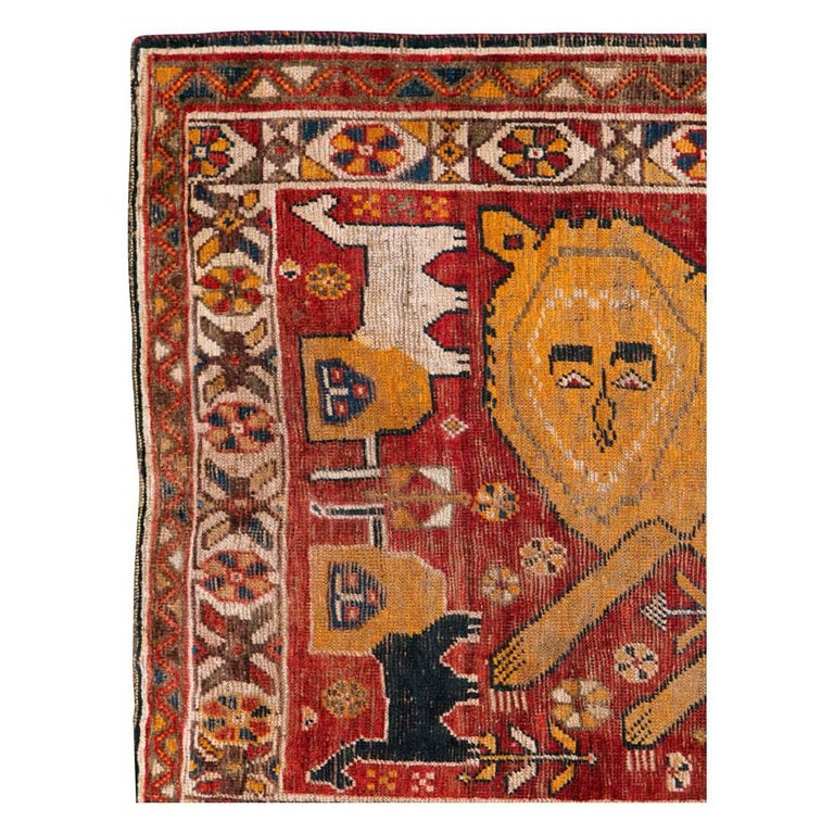 An antique Persian Gabbeh tribal rug handmade by the nomadic Qashqai tribe in South Persian during the early 20th century. One large orange folksy lion prances over the deep red field and is surrounded by 4 smaller black and white lions. This