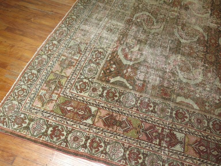 A distressed room size Persian Malayer rug from the early 20th century.