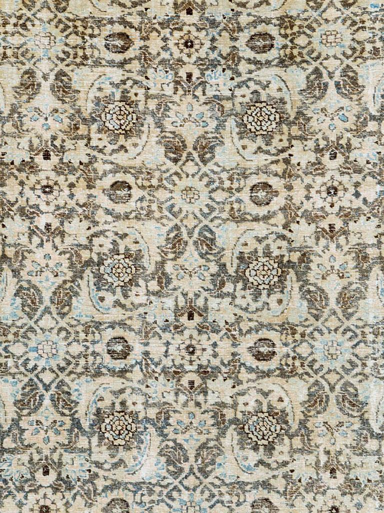 A vintage Persian Tabriz room size carpet with a distressed appeal from the mid-20th century. The all-over Herati pattern is dressed in nude and slate blue over a charcoal brown field. The reversing turtle design in the border is in charcoal brown