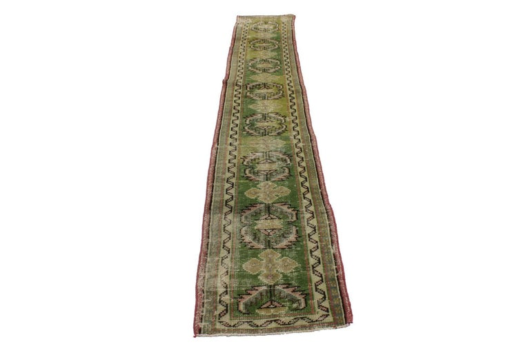 51713, distressed vintage Turkish green Oushak runner, narrow hallway. This hand-knotted wool distressed vintage Turkish Oushak runner features alternating amulet medallions with serrated edges and equilateral cruciform motifs in an abrashed field.