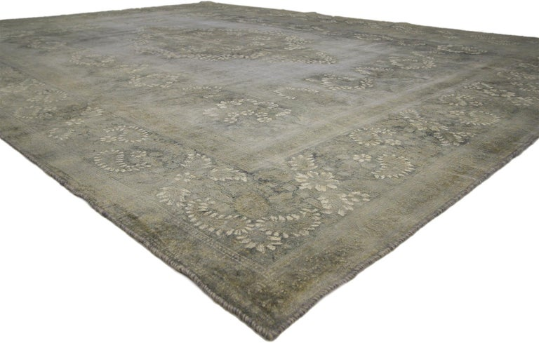 60762, distressed vintage Turkish rug with rustic French Farmhouse style. This distressed vintage Turkish rug showcases a brilliant French floral medallion on an ethereal gray field surrounded by matching star-flower garlands in attached pendants,