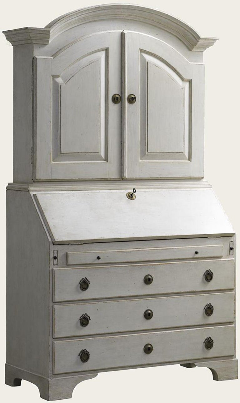 Distressed white painted Gustavian style bureau - secretaire. Hand carved and hand painted adds warmth to any room with it's great dimensions and country style coloring. Three shelves, numerous small drawers in the bureau bottom-half and larger