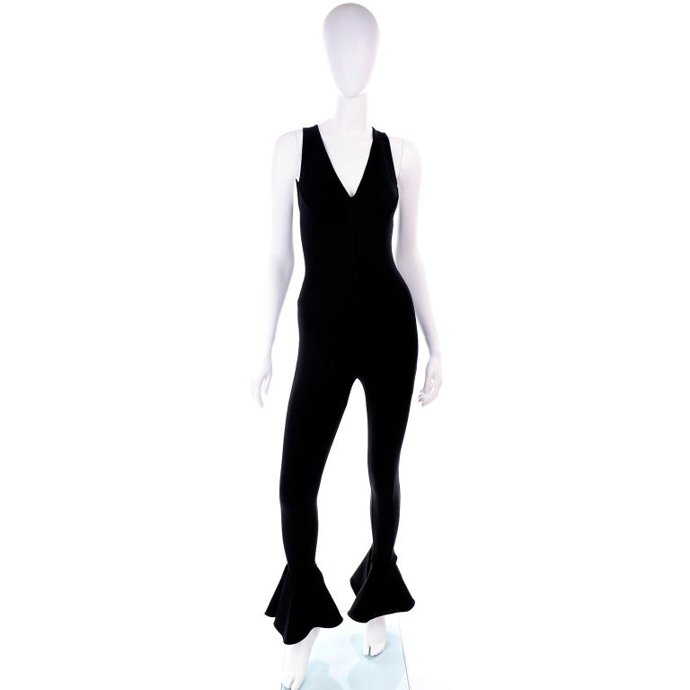 This is an iconic Versace black stretch jumpsuit with a ruffled hem designed by Gianni Versace for his 1993 Spring Summer collection.  This show stopping  jumpsuit is 90% rayon, 8% nylon and 2% spandex.  There is a metal back seamless zipper for