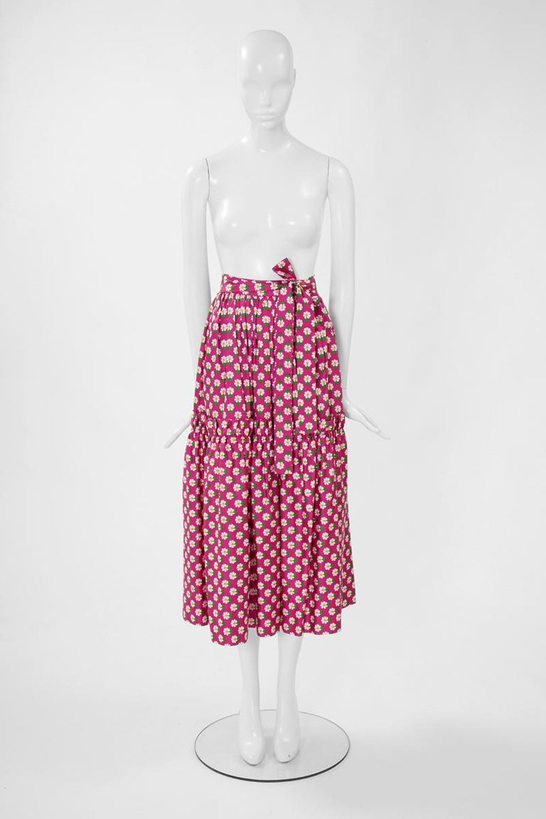 From the iconic SS1977 YSL collection, this skirt is entirely printed with daisies that evoke the freshness of the Spring. The daisies really pop up against the vivid fuchsia background ! Constructed in a kind of sateen cotton, this ruffled (see
