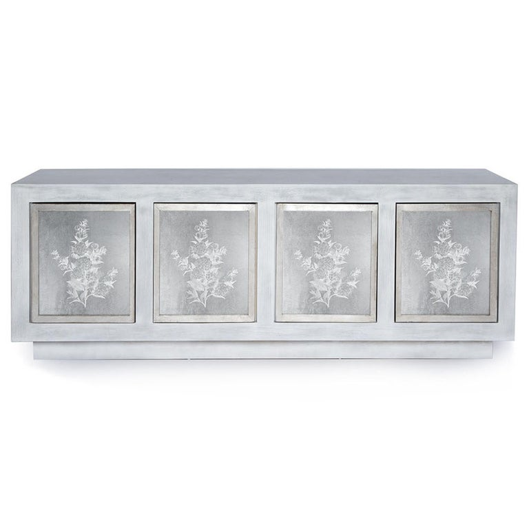 The Doheny Credenza is a beautifully unique piece, made of solid wood. Hand embellished glass panels are set against the four wooden doors for a highly stylized appeal. Door frames are in a metallic, hand-gilded nish for an added touch of glamour.